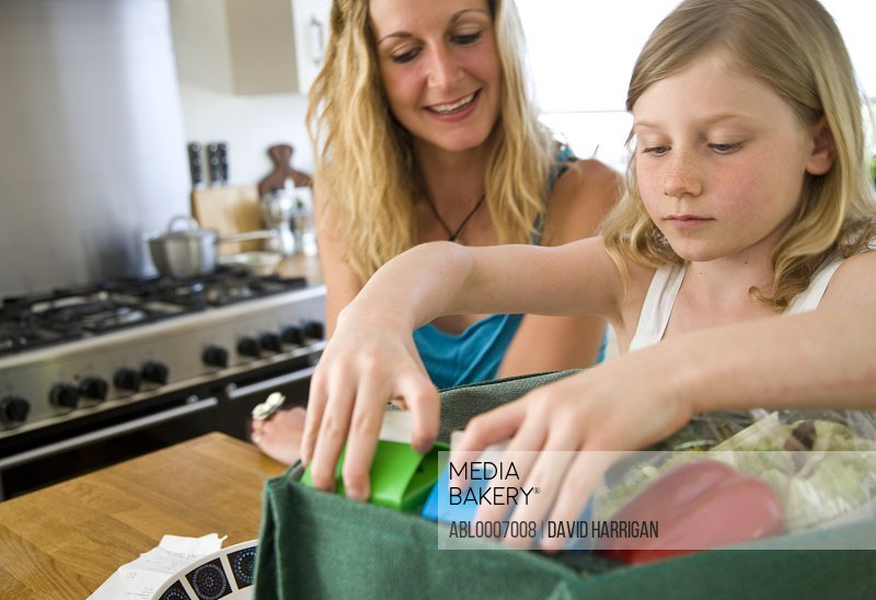Mother and Daughter Unpacking Groceries