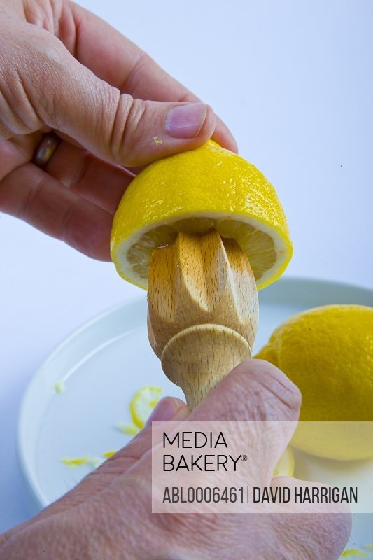 Man's Hands Squeezing Lemon with Juicer