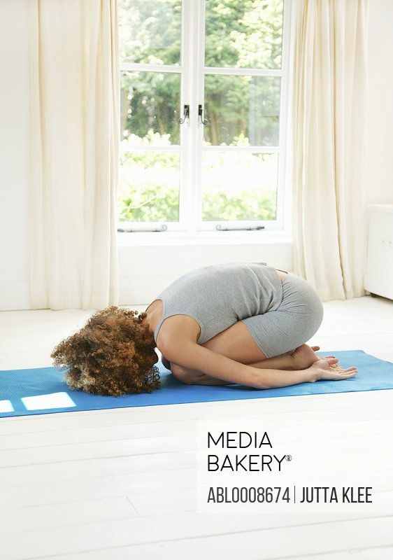Woman Practicing Yoga in the Child's Pose