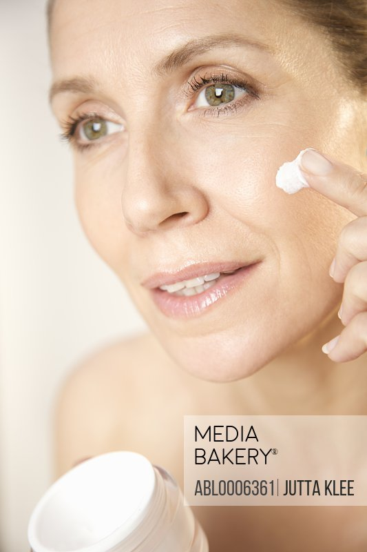 Close up of a woman applying cosmetic cream