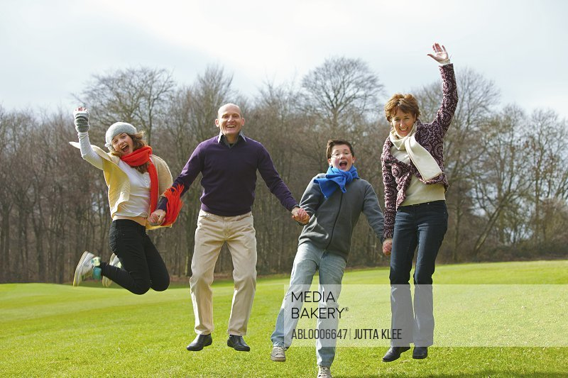 Smiling Family Holding Hands and Jumping in Park