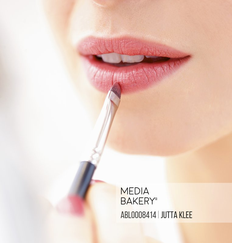 Woman Applying Lipstick with Makeup Brush, Close-up View