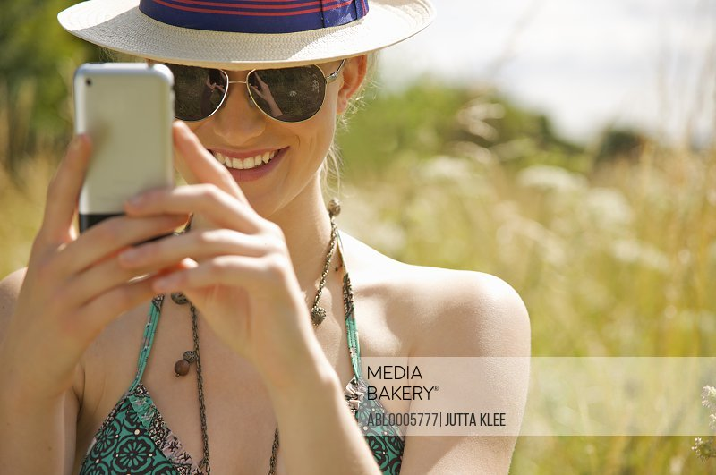 Smiling young woman using a mobile phone