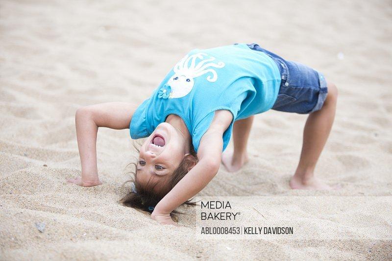 Girl Doing Wheel Pose on Sand