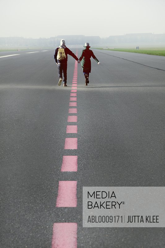 Couple Running along Airport Runway Holding Hands, Rear View