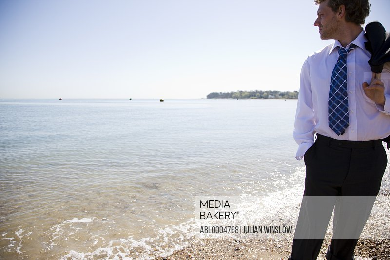 Young businessman on a beach walking with jacket over his shoulder
