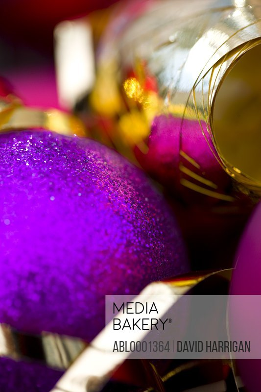 Extreme close up of a purple Christmas bauble and a gold ribbon
