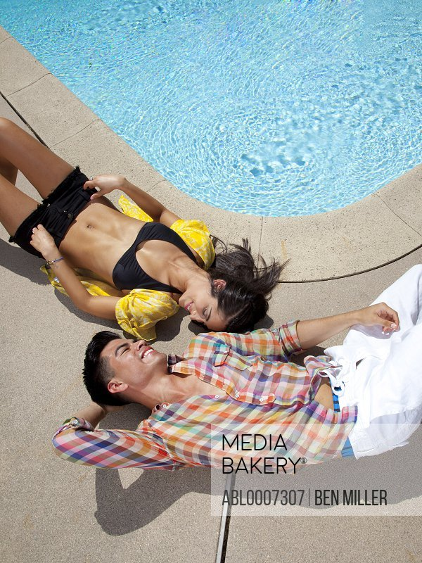 Couple Sunbathing on the Edge of Swimming Pool, High Angle View