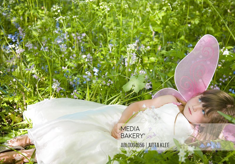 Portrait of a girl in a fairy costume lying in a field of flowers