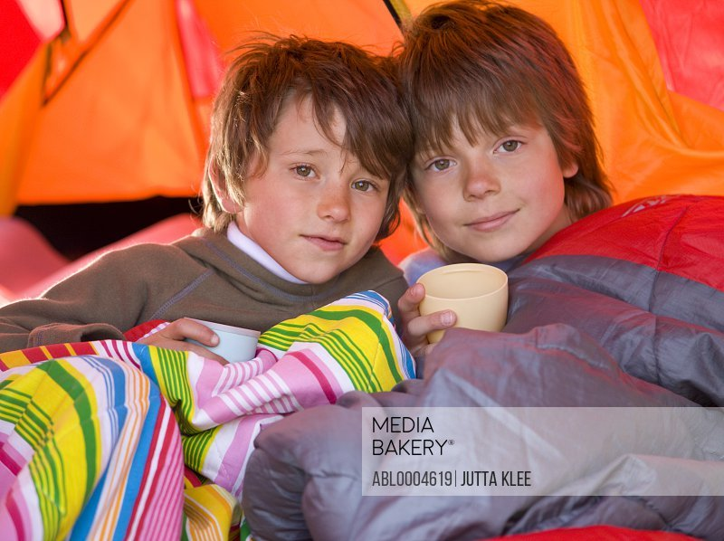 Portrait of two boys sitting in a tent in sleeping bags