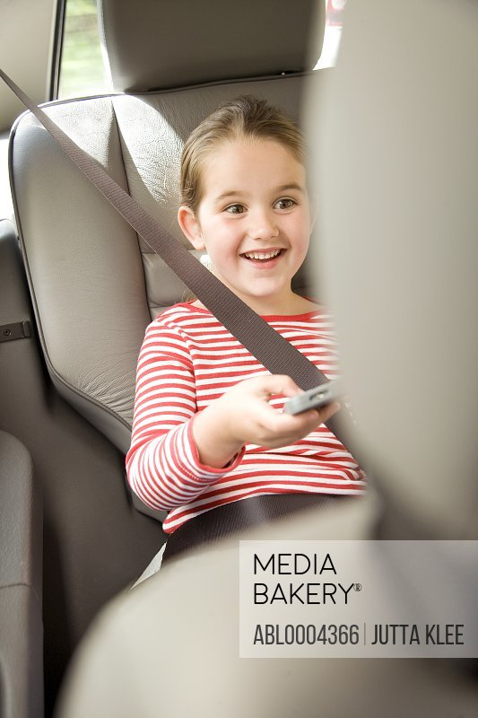 Portrait of a girl playing game inside car