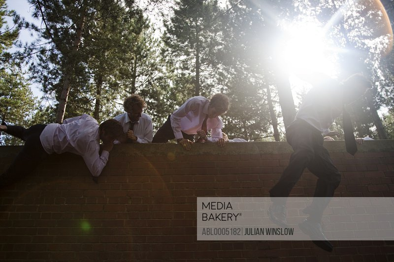 Businessmen at an obstacle course climbing a brick wall
