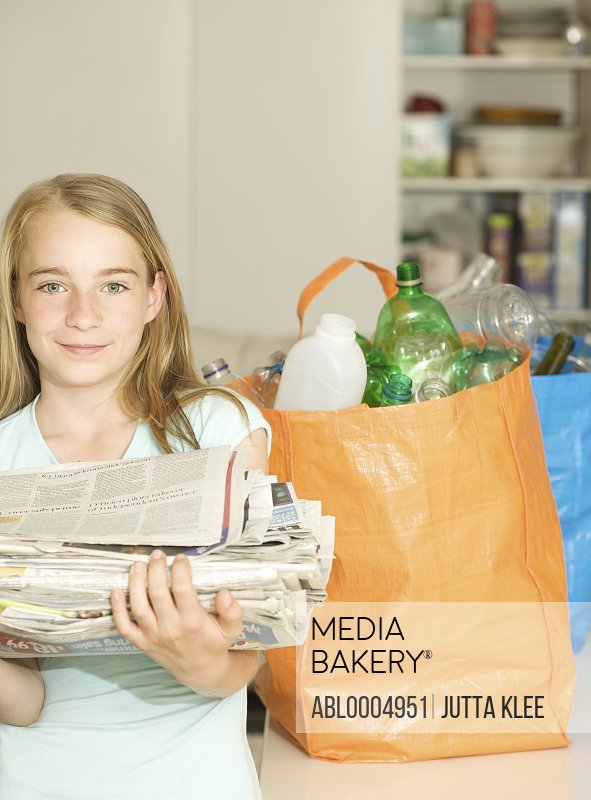 Young girl standing next to recycling bags holding a pile of newspapers