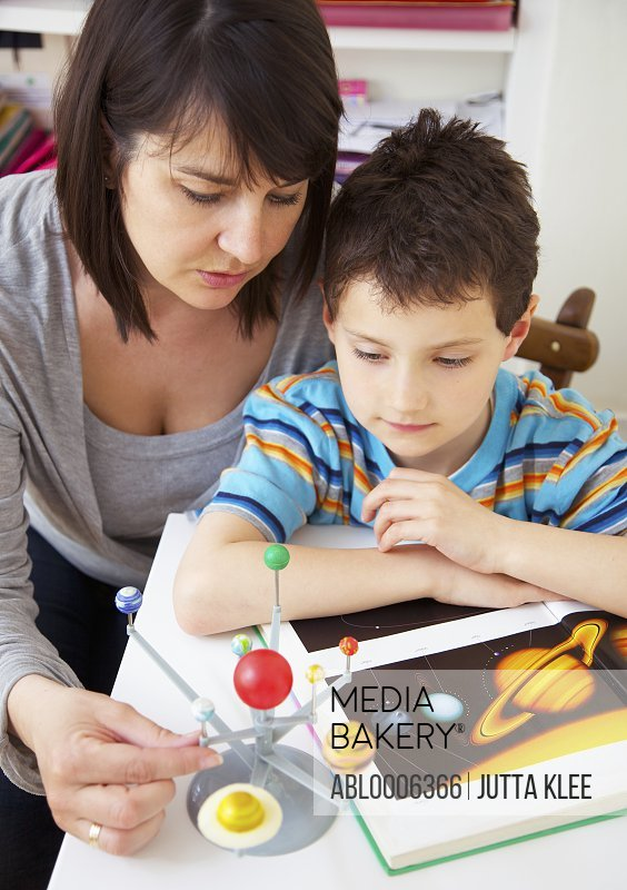 Woman and Young Boy Inspecting Solar System Model