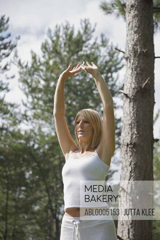 Young woman doing yoga standing in a forest in the raised hands pose