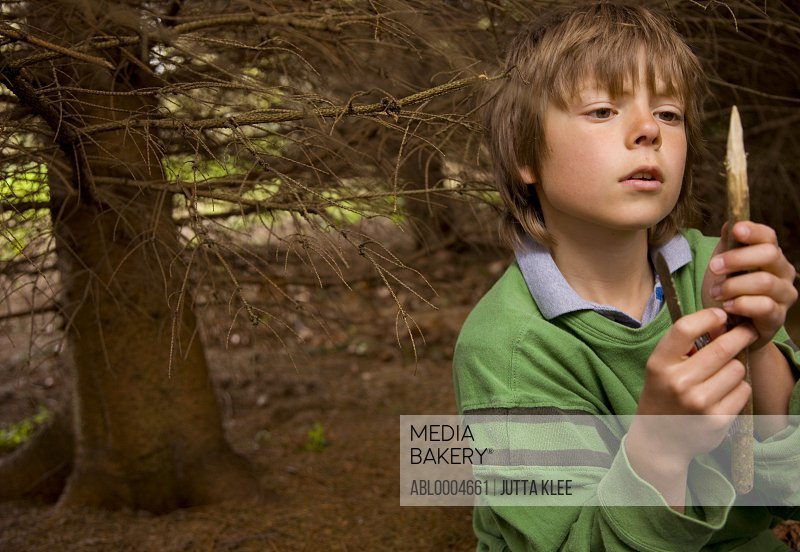 Portrait of a boy sharpening a wooden stick in a campsite