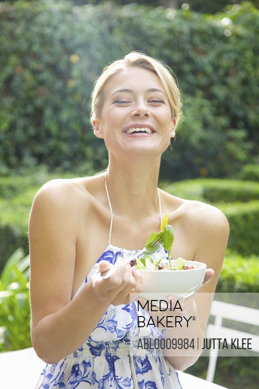 Woman Eating Salad in Garden Smiling