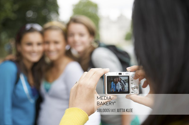 Back view of a woman taking photograph of three teenaged girls with digital camera