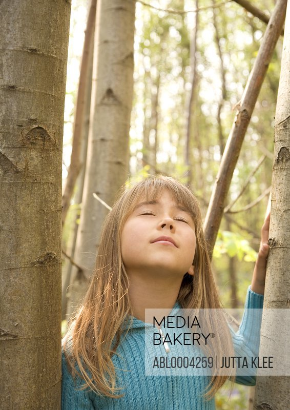 Young girl standing amongst tree with eyes closed