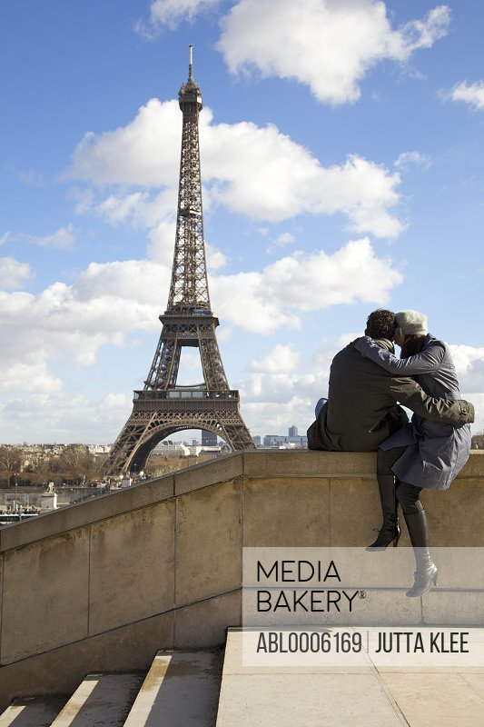 Back view of a couple sitting on a wall in front of the Eiffel Tower