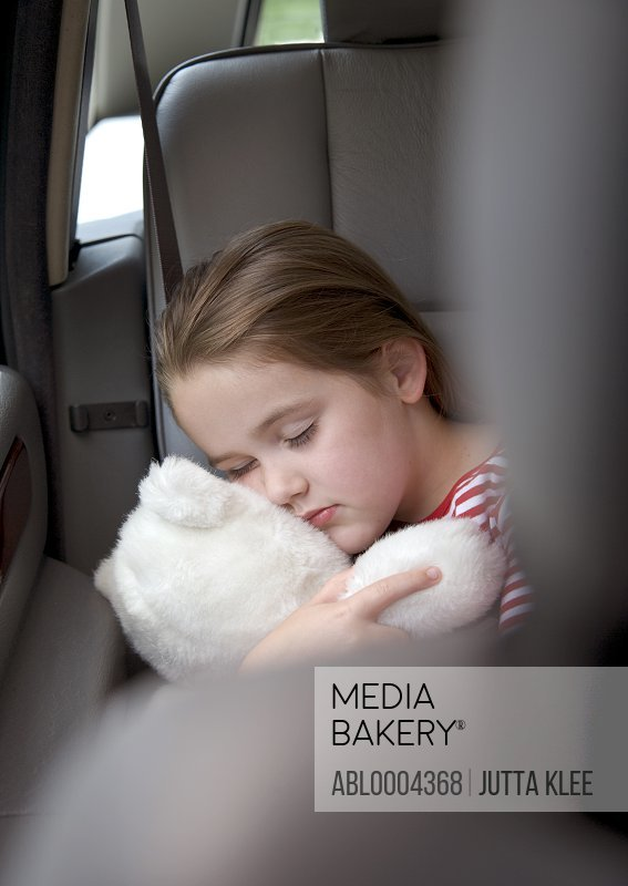 Portrait of a girl sleeping and cuddling teddy bear