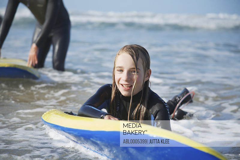 Smiling and wet girl in the sea holding on to her surfboard