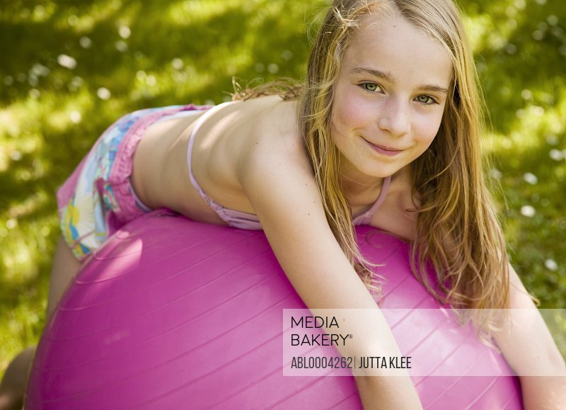 Portrait of Girl lying on pink ball smiling