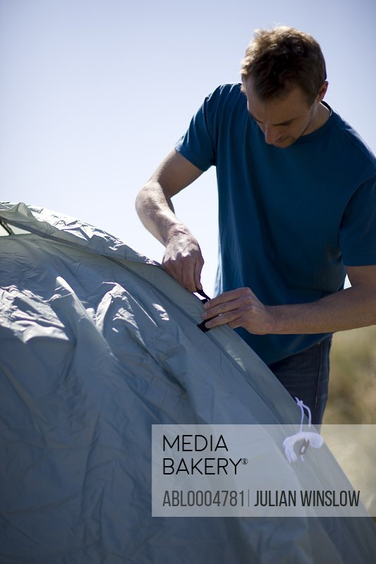 Portrait of a man standing and erecting tent