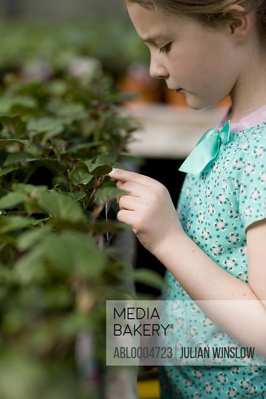 Young girl touching a plant in a nursery