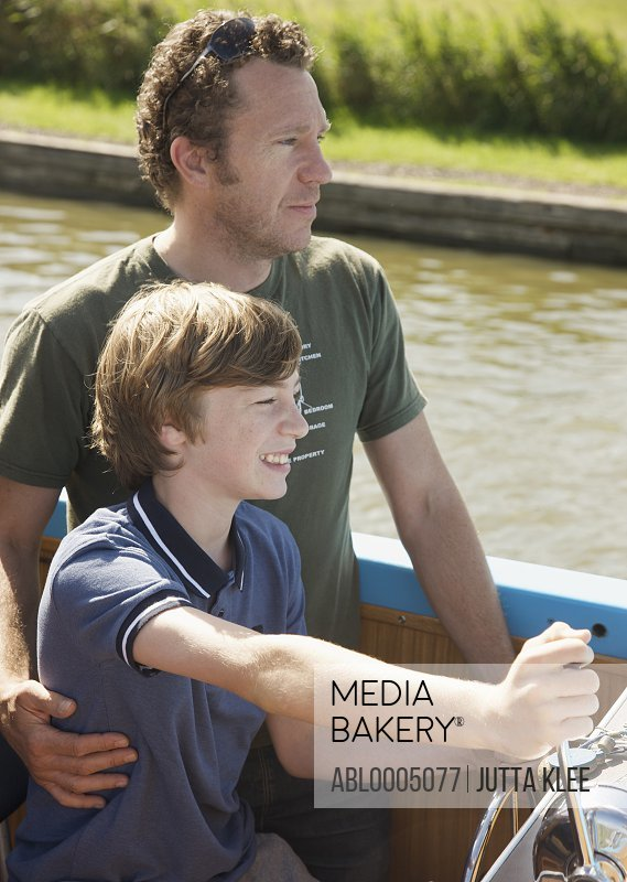 Man and smiling teenaged boy steering a boat