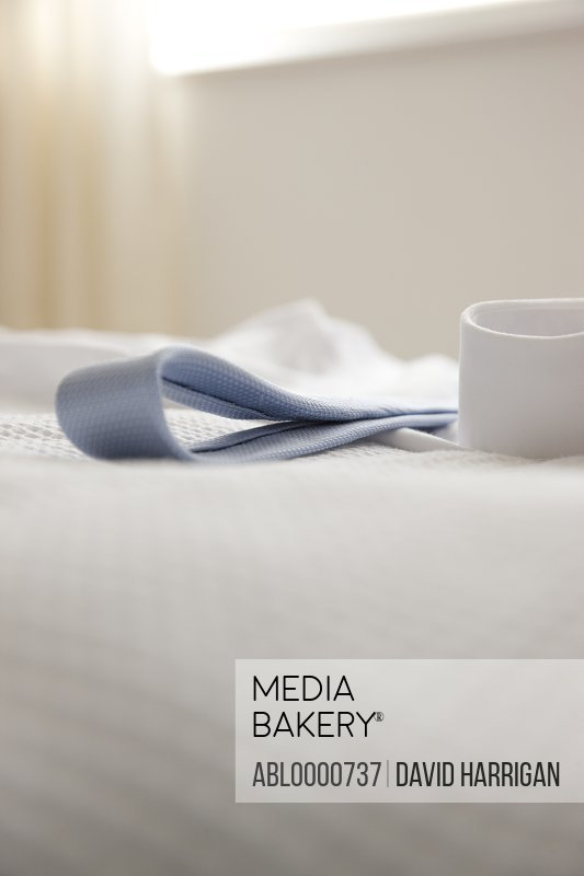 Detail of shirt cuff and tie lying on a bed