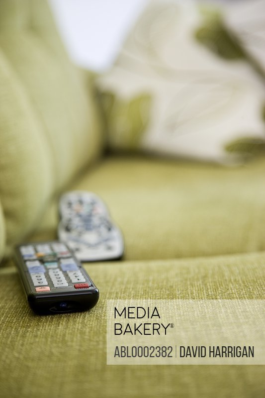 Remote Controls on Green Sofa