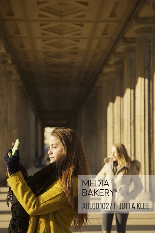 Teenage Girl Taking Photograph under Colonnade of Old National Gallery, Alte Nationalgalerie, Berlin Germany