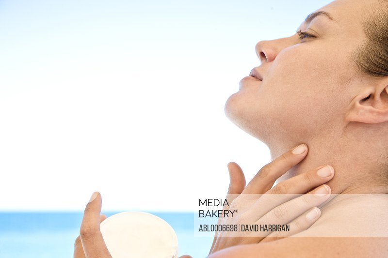 Young Woman Applying Moisturizer on Neck