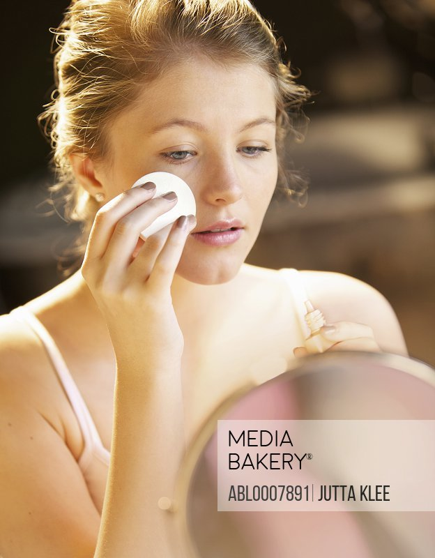 Young Woman Applying Makeup with Cotton Pad