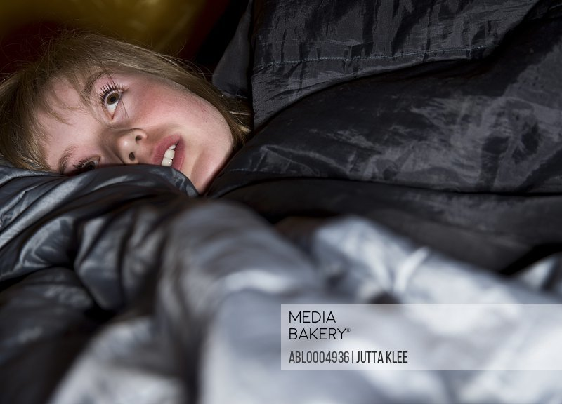 Close up of teenaged girl wrapped in a sleeping bag lying down and looking up with apprehension