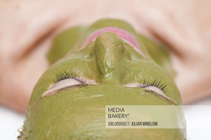 Extreme close up of a woman with green facial mask - upside down
