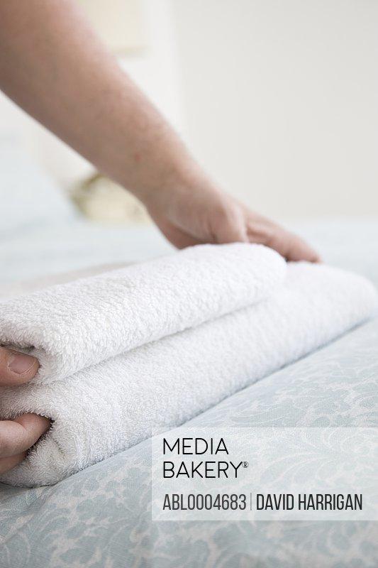 Close up of man hands adjusting towel on bed