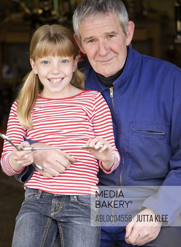 Portrait of grandfather and granddaughter holding wrenches smiling