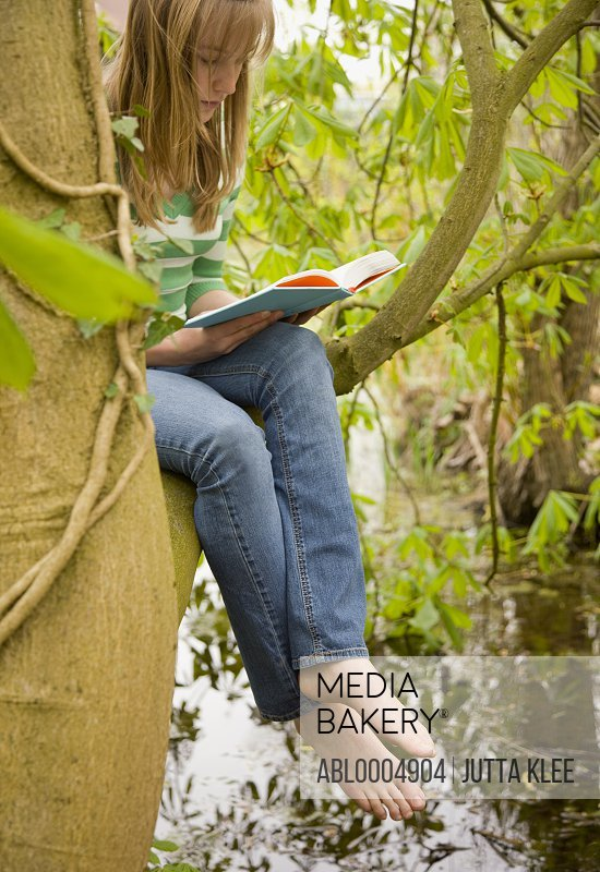 Teenaged girl sitting on a the bough of a tree reading a book
