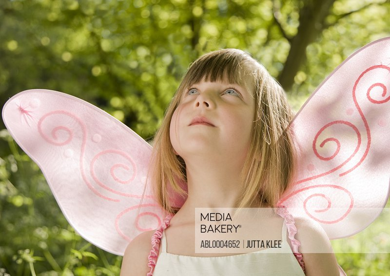 Girl in a pink fairy costume looking up