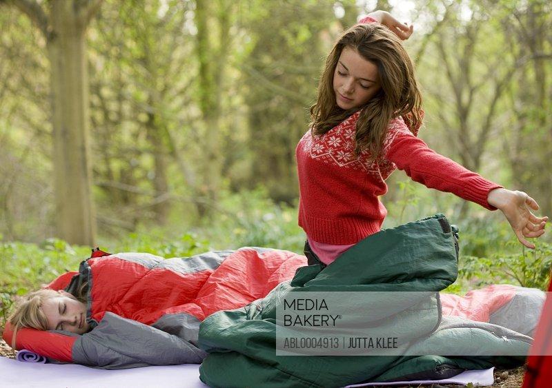 Teenaged girl at campsite kneeling inside sleeping bag stretching arms