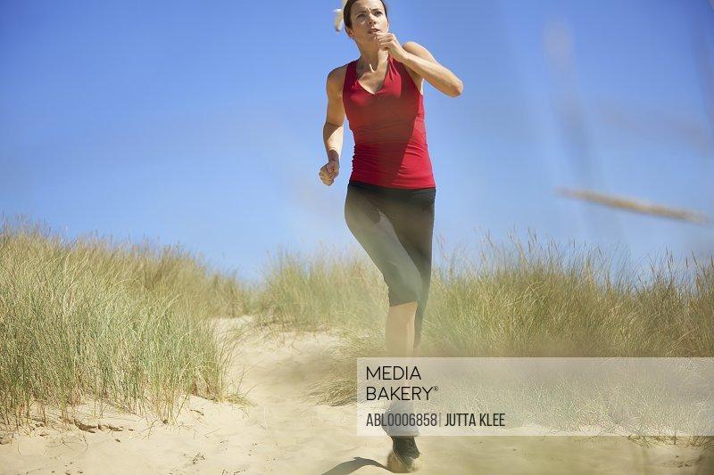 Woman Running on Sand Dune