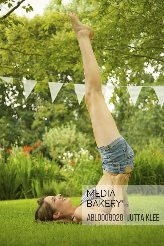 Teenage Girl Doing Shoulder Stand in Garden