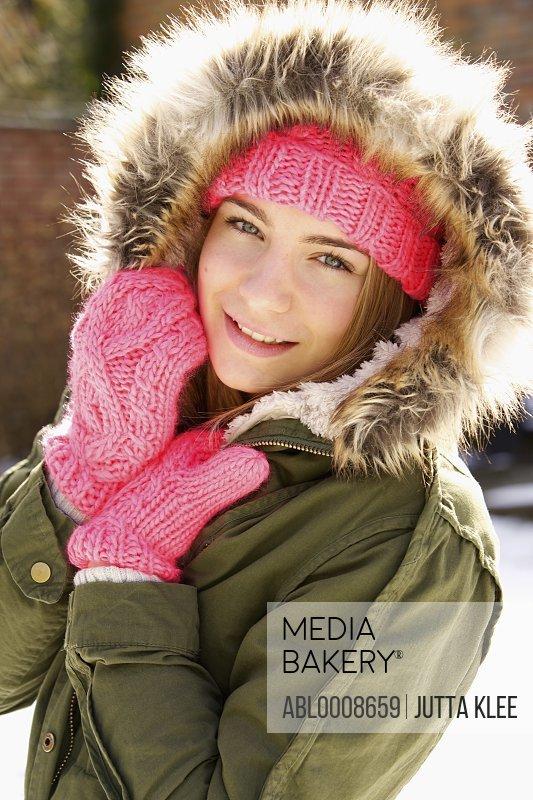 Smiling Teenage Girl Wearing Hooded Parka Outdoors