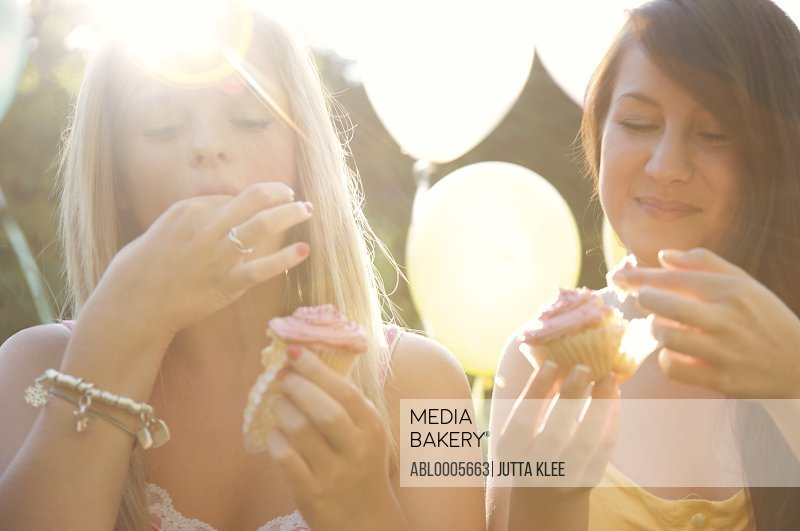 Teenage girls at birthday party eating cupcakes