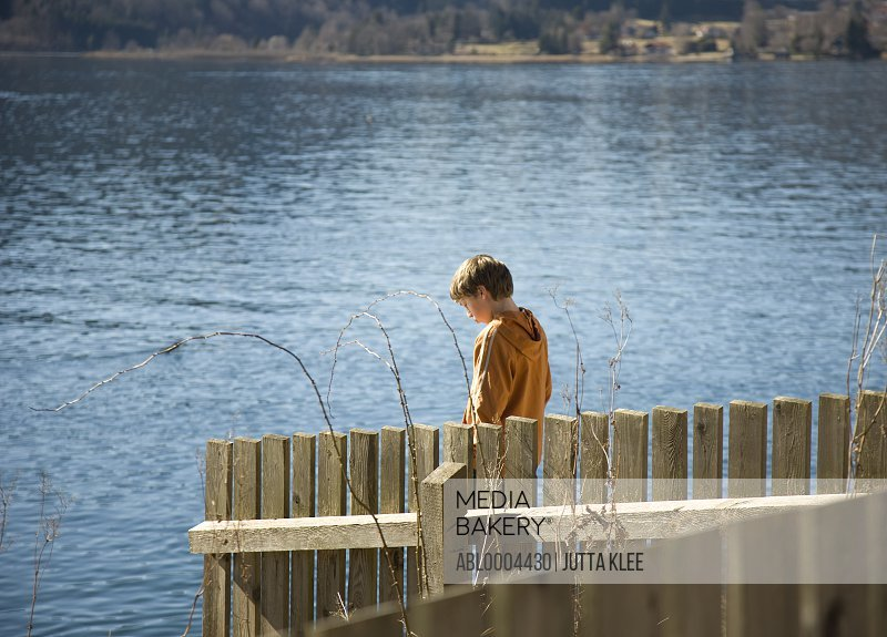 Portrait of young boy walking by lake