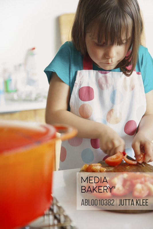 Young Girl Cutting Tomatoes