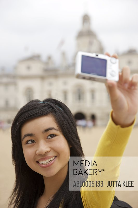 Teenaged girl taking self portrait with digital camera in front of London Horse Guards Parade