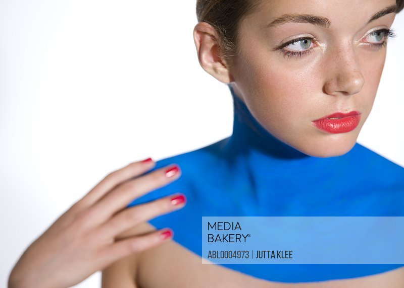 Young woman with décolletage painted with electric blue body paint
